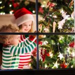 Two children, both wearing Christmas outfits, are decorating a Christmas tree. The photo supports article called