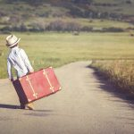 A stock photo of a boy carrying a suitcase