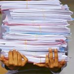 A photo of a person carrying a pile of documents