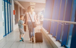 A photo of a mother and son with a suitcase at the airport