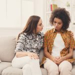 Two sad diverse women talking at home. Female friends supporting each other. Problems, friendship and care concept