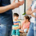 COVID-19 and Domestic Violence Help. Accompanying image: children watching their parents quarreling at home
