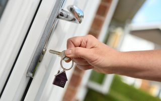 Who Stays In The House? Accompanying image: opening a door to house with key
