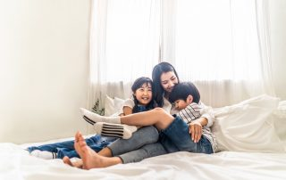 Setting aside a binding child support agreement. Accompanying image: mother, son and daughter sit on bed with happiness and smile in bedroom.
