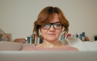 Staying safe in an online world: Beautiful Lady with Laptop in a Cozy Room.